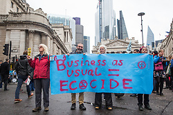London, UK. 14 October, 2019. Climate activists from Extinction Rebellion block a road in front of the Bank of England with a banner reading 'Business as usual = ecocide' on the eighth day of International Rebellion protests across London.