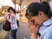 """31 JANUARY 2013 - PHNOM PENH, CAMBODIA:   A Cambodian woman prays for former King Norodom Sihanouk in front of the Royal Palace in Phnom Penh. Sihanouk (31 October 1922- 15 October 2012) was the King of Cambodia from 1941 to 1955 and again from 1993 to 2004. He was the effective ruler of Cambodia from 1953 to 1970. After his second abdication in 2004, he was given the honorific of """"The King-Father of Cambodia."""" Sihanouk served two terms as king, two as sovereign prince, one as president, two as prime minister, as well as numerous positions as leader of various governments-in-exile. He served as puppet head of state for the Khmer Rouge government in 1975-1976. Most of these positions were only honorific, including the last position as constitutional king of Cambodia. Sihanouk's actual period of effective rule over Cambodia was from 9 November 1953, when Cambodia gained its independence from France, until 18 March 1970, when General Lon Nol and the National Assembly deposed him. Upon his final abdication, the Cambodian throne council appointed Norodom Sihamoni, one of Sihanouk's sons, as the new king. Sihanouk died in Beijing, China, where he was receiving medical care, on Oct. 15, 2012. His funeral procession, which will wind through Phnom Penh is Friday, Feb.1 and his cremation is on Feb. 4, 2013. Over a million people are expected to attend the service.   PHOTO BY JACK KURTZ"""