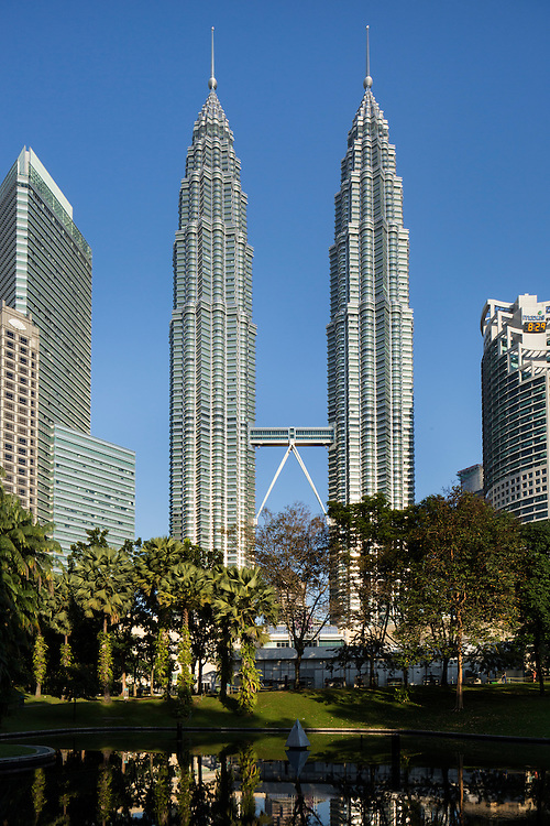 Malaysia, Kuala Lumpur, Twin towers of the 88 story tall Petronas Towers skyscraper rises above forested public park