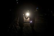 Two women walking hand in hand on a dark street in the north of Gaza City. Due donne si tengono per la mano mentre camminano al buio in una strada al nord di Gaza City.