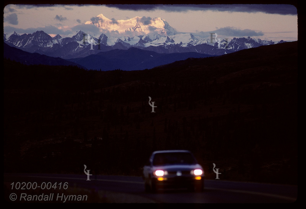 Distant snowy mountains catch August sunset as car drives into dark with headlights on; Denali National Park, Alaska