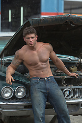 shirtless man with tattoos leaning against a old car with an open hood in the rain