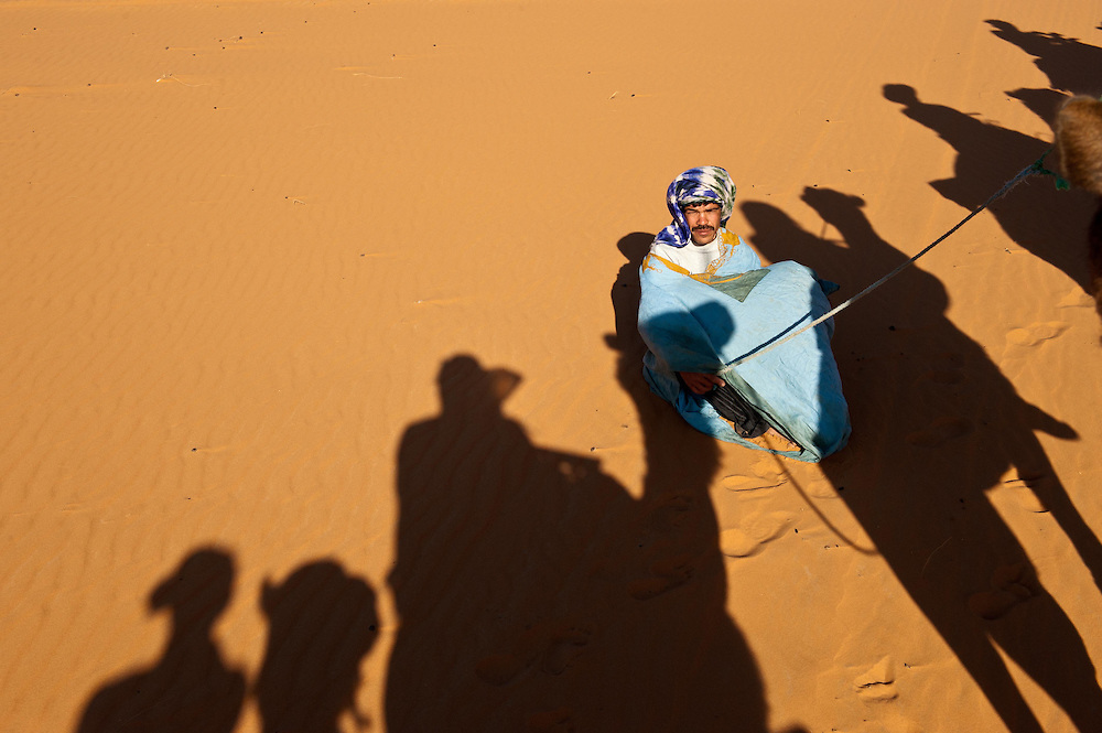 Berber sits in the shadow of tourists getting a camel ride