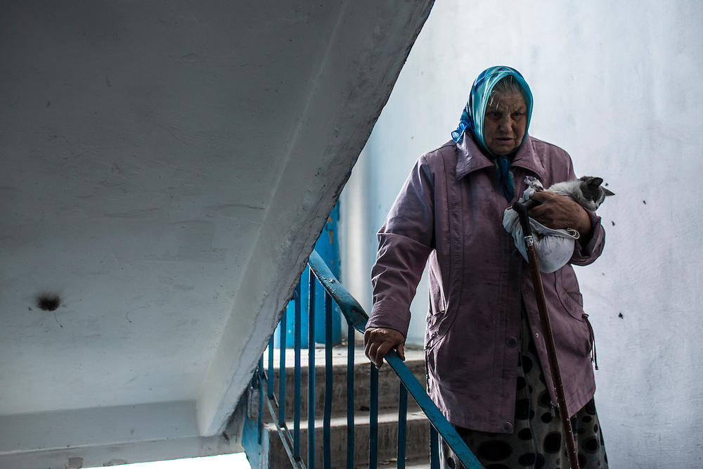 Nadezda Panasyk, 75, with her cat Pushok (Fluffy) in the stairwell of her apartment building in the Kievsky district where she lives on Friday, October 17, 2014 in Donetsk, Ukraine. Her building is used by fighters for the Donetsk People's Republic to coordinate efforts to gain control of the Donetsk airport, one of the most heavily contested ongoing battles of the war in Eastern Ukraine. Photo by Brendan Hoffman, Freelance