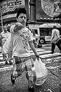 A young Latino man carrying his deliveries crossing Time Square and 42nd Street.