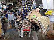 PENNDEL, PA -  MARCH 5: Catherine Galloway (R) of Mt. laurel, New Jersey, Jaden Fernandez, (C) 6 years old, and Nancy Galloway of Cherry Hill, New Jersey carry wool as the exit March 5, 2014 during a free-wool giveaway at Legendary Langhorne Carpet in Penndel, Pennsylvania. The free fleece survived Langhorne's electrical fire last summer and the family-owned carpet mill, which is in the process of restocking with new shipments, decided the 'surplus' should be recycled on looms rather than dumped into landfills.  (Photo by William Thomas Cain/Cain Images)