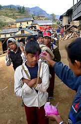 A Maoist commander puts a tikka on villagers as they begin work for 15 days to construct  the road from Rolpa to Thabang in Tila village, Rolpa district in western Nepal March 13, 2005. Ami Vitale