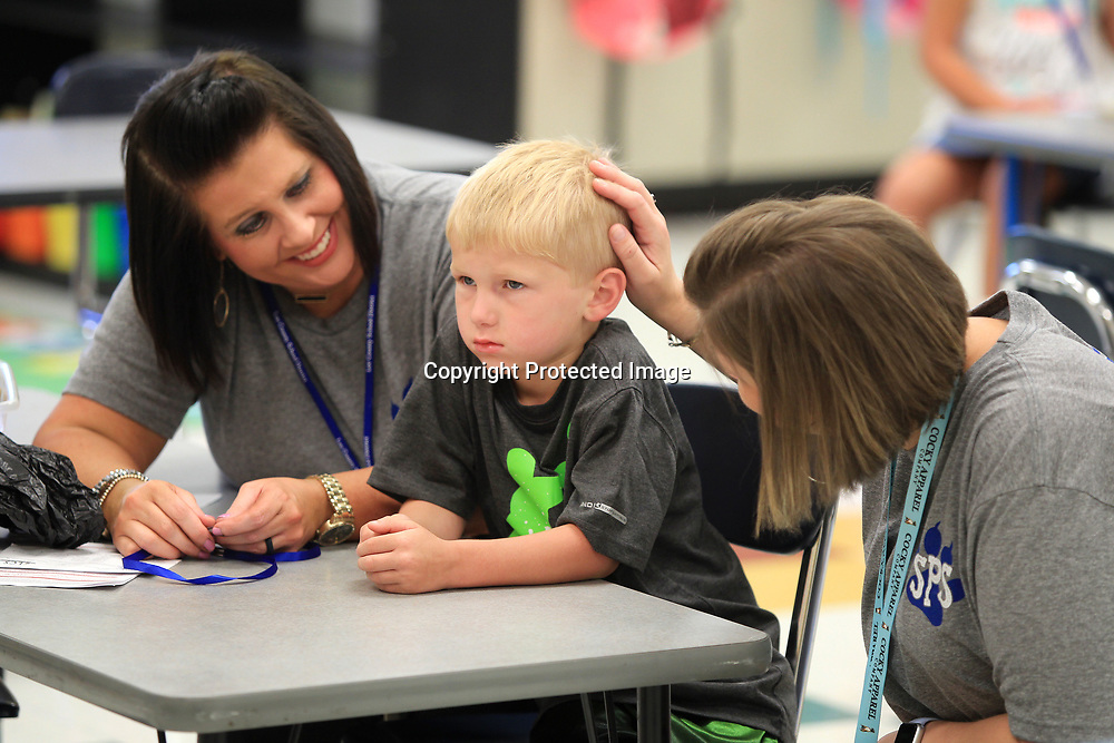 Saltillo Primary School kindergarten teachers Rhiannon Waddell, left, and Emily Burns, do their best to cheer up and encourage new student Caleb Myhand on his first day to school on Thursday morning in Saltillo.