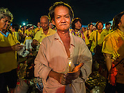 05 DECEMBER 2014 - BANGKOK, THAILAND: A woman holds a candle on Sanam Luang for the celebration of the King's Birthday. Thais marked the 87th birthday of Bhumibol Adulyadej, the King of Thailand, Friday. The King was born on December 5, 1927, in Cambridge, Massachusetts. The family was in the United States because his father, Prince Mahidol, was studying Public Health at Harvard University. He has reigned since 1946 and is the world's currently reigning longest serving monarch and the longest serving monarch in Thai history. Bhumibol, who is in poor health, is revered by the Thai people. His birthday is a national holiday and is also celebrated as Father's Day. He is currently hospitalized in Siriraj Hospital, recovering from a series of health setbacks.     PHOTO BY JACK KURTZ