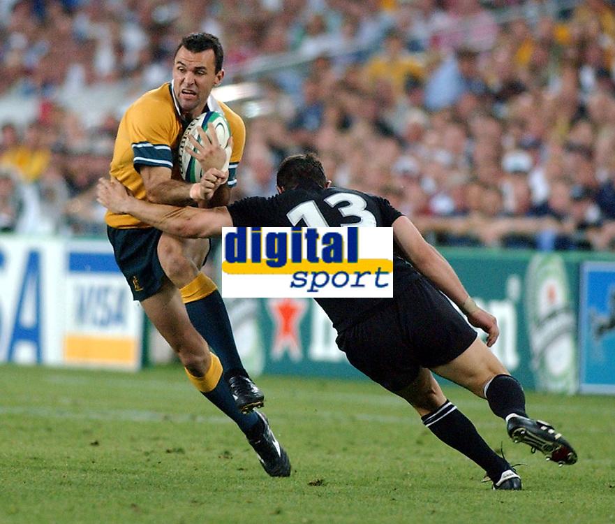 Photo. Steve Holland.Australia v New Zealand, Semi-final at the Telstra Stadium, Sydney. RWC 2003.<br />15/11/2003.<br />Joe Roff  tackle by MacDonald, right