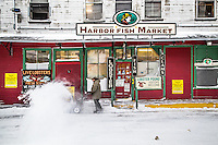 A man pushes a snowblower in front of Harbor Fish Market in Portland, Maine.