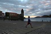Boy walking on Boramar beach, with the Eglise Notre Dame des Anges in the background, Collioure, France. The bell tower was converted from a medieval lighthouse and the Mediterranean Gothic style nave was built in 1684. The dome was added to the bell tower in 1810. Picasso, Matisse, Derain, Dufy, Chagall, Marquet, and many others immortalized the small Catalan harbour in their works. Picture by Manuel Cohen.