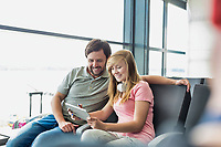 Portrait of young beautiful teenage girl showing digital tablet to her father while sitting and waiting for their flight in airport