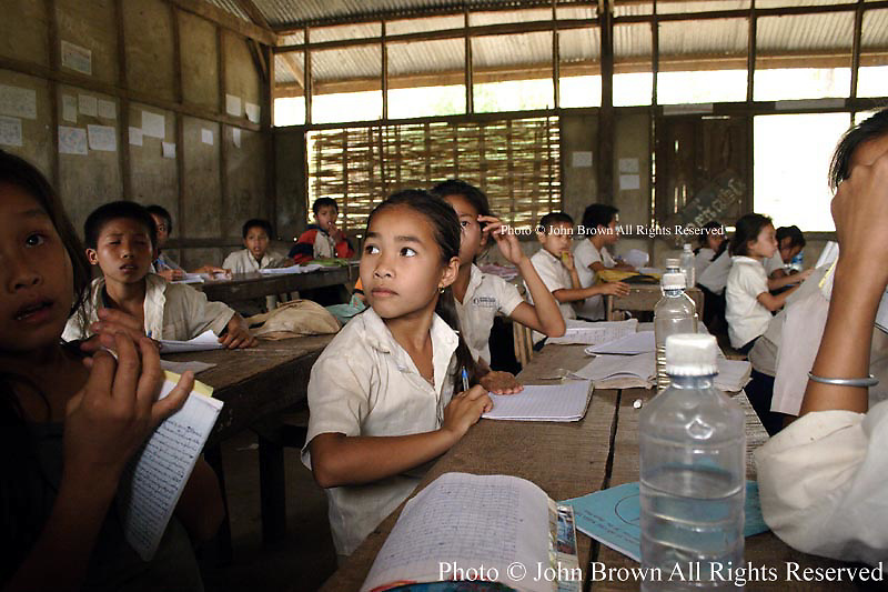 Students sit at their learning tables at The Ban Buamlao Primary School in Ban Buamlao, Laos. Since 70% of the Lao population does not have daily access to potable drinking water, students must purchase bottled water. The school has no water supply or electricity.