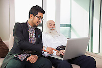 Grandfather and grandson using laptop in living room