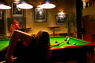 Hangzhou, China. Bar on the popular downtown Nanshan Road. Two young women playing pool