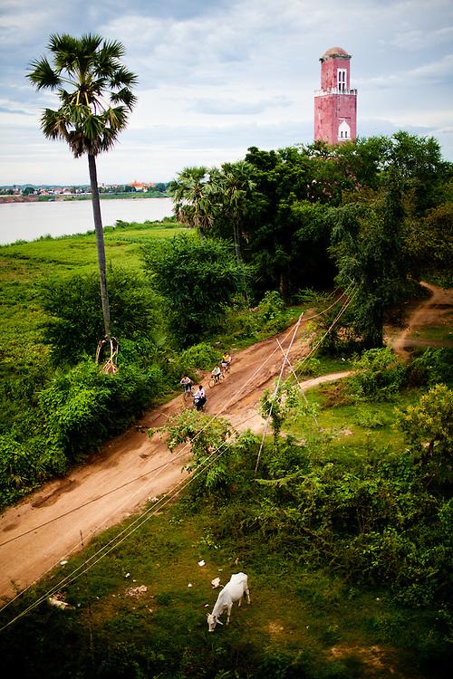 Ein alter franzoesischer Leuchtturm am Ufer des Mekong. Im Vordergrund Kinder mit Fahrrad und eine grasende Kuh. In Kampong Cham, Kambodscha.