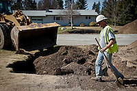JEROME A. POLLOS/Press..Kevin O'Steen, with SI Construction, works in a drywell Monday on 15th Avenue and Henry Street in Post Falls. A street widening project to allow for bike lanes is causing many residents to sign a petition asking the city for exceptions to a future no parking rule on 15th Avenue once the bike lanes are completed.