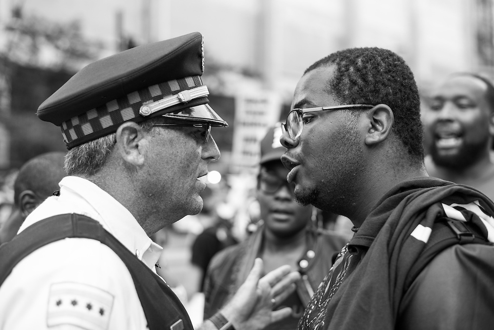 A protester confronts a Chicago Police officer after police forcibly removed people from the street during a march against ongoing police violence in Chicago on July 9, 2016.
