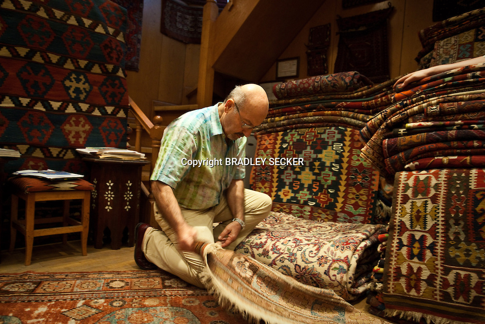 ISTANBUL, TURKEY, JUNE 2012: Erol Kazanci, the owner of Galleri Shirvan, inspects two carpets brought to him from Central Asia for restoration by a British collector. Grand Bazaar. (Photo by Bradley Secker for the Washington Post)