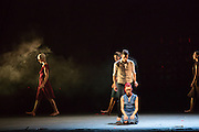 "With a man and a woman at the front of the stage, dancers cross behind and into the fog in Barak Marshall's ""Harry""."