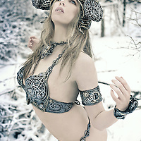 A powerful young woman wearing a metal bikini in the snowy woods staring up at the sky