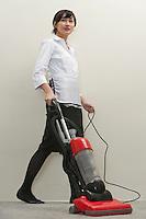 Full length of young female housekeeper vacuuming