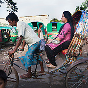 A rickshaw driver with his customer next to the train tracks and the Tejgaon slums. Rickshaws are the cheapest and most commonly used mode of public transport in Dhaka.