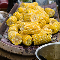 Charcoal roasted corn on a large wooden platter at an outdoor farm feast.