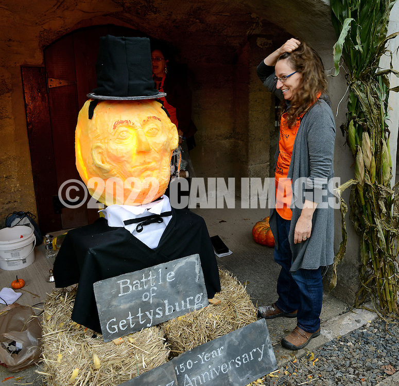 DOYLESTOWN, PA -  OCTOBER 19:  Lisa Naples of Doylestown, Pennsylvania looks at a pumpkin carved with the likeness of Abraham Lincoln during Pumpkinfest at the Moravian Tile Works October 19, 2013 in Doylestown, Pennsylvania. (Photo by William Thomas Cain/Cain Images)
