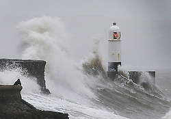 © Licensed to London News Pictures. 03/02/2017<br /> <br /> A man looks on as huge waves strike the harbour wall and lighthouse at Porthcawl, south Wales, as strong winds and heavy rain batters the south west of England and south Wales, with gusts reaching up to sixty miles per hour in places, Friday 03 February 2017.<br /> <br /> Photo credit: Geoff Caddick/ LNP