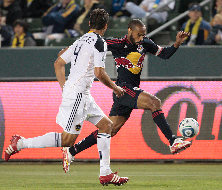 New York Red Bulls forward Thierry Henry of France, right, moves the ball defended by Los Angeles Galaxy defender Omar Gonzalez during the first half of a MLS soccer match, Saturday, May 7, 2011, in Carson, Calif. (AP Photo/Jason Redmond)