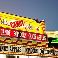 Photo of carnival ride and concession stand food sign with cotton candy, candy apples, and popcorn.  Photo is high resolution.