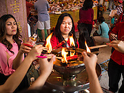 "07 FEBRUARY 2016 - BANGKOK, THAILAND: People make merit for Chinese New Year at the Poh Teck Tung Shrine, a popular Chinese shrine in Bangkok's Chinatown. Chinese New Year, also called Lunar New Year or Tet (in Vietnamese communities) starts Monday February 8. The coming year will be the ""Year of the Monkey."" Thailand has the largest overseas Chinese population in the world; about 14 percent of Thais are of Chinese ancestry and some Chinese holidays, especially Chinese New Year, are widely celebrated in Thailand.        PHOTO BY JACK KURTZ"