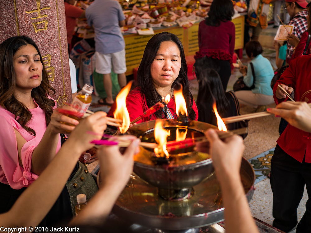 """07 FEBRUARY 2016 - BANGKOK, THAILAND: People make merit for Chinese New Year at the Poh Teck Tung Shrine, a popular Chinese shrine in Bangkok's Chinatown. Chinese New Year, also called Lunar New Year or Tet (in Vietnamese communities) starts Monday February 8. The coming year will be the """"Year of the Monkey."""" Thailand has the largest overseas Chinese population in the world; about 14 percent of Thais are of Chinese ancestry and some Chinese holidays, especially Chinese New Year, are widely celebrated in Thailand.        PHOTO BY JACK KURTZ"""