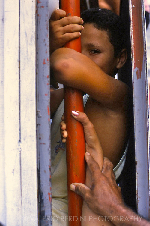 A child takes shelter from the crowd in a scaffolding.