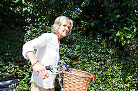 Senior woman looking away while standing with bicycle at backyard