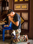 25 MARCH 2016 - BANGKOK, THAILAND: A man prays in the doorway of the church during Good Friday observances at Santa Cruz Church in Bangkok. Santa Cruz was one of the first Catholic churches established in Bangkok. It was built in the late 1700s by Portuguese soldiers allied with King Taksin the Great in his battles against the Burmese who invaded Thailand (then Siam). There are about 300,000 Catholics in Thailand, in 10 dioceses with 436 parishes. Good Friday marks the day Jesus Christ was crucified by the Romans and is one of the most important days in Catholicism and Christianity.      PHOTO BY JACK KURTZ