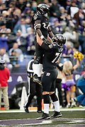 Baltimore Ravens running back Alex Collins (34) gets a lift in the air by Baltimore Ravens offensive guard Alex Lewis (72) as the two celebrate after Collins runs for a 7 yard touchdown good for a 7-0 first quarter Ravens lead during the NFL week 11 regular season football game against the Cincinnati Bengals on Sunday, Nov. 18, 2018 in Baltimore. The Ravens won the game 24-21. (©Paul Anthony Spinelli)