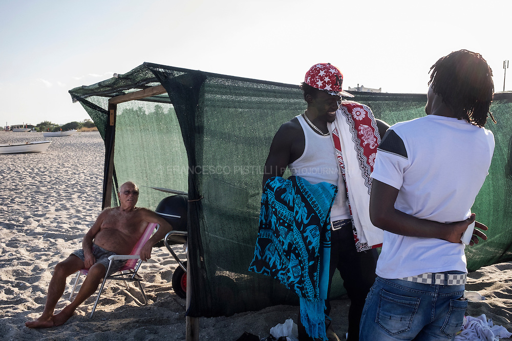 Antonio, a local fisherman, Sheriffo from Gambia and his Gambian friend Seedy are taking a rest from work, sharing the same shadow of a shanty used for housing boats.  RIACE (ITALY) 03/08/16