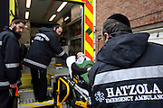 Hatzola are a voluntary medical emergency service that provides care to the Orthodox Jewish community of North London.  Here 3 of their volunteers assist an Orthodox Jewish patient wearing an oxygen mask into the back of their ambulance.