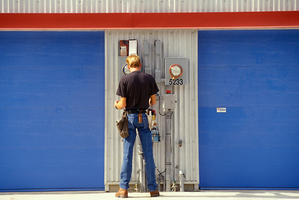 Stock photo of a man standing outside reading measurements from meters on a building