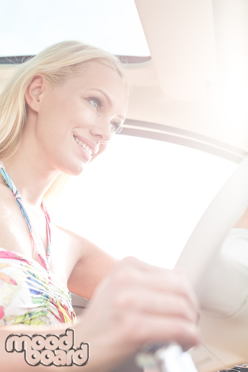 Low angle view of smiling woman driving car