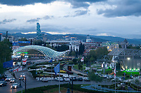 evening view of the Bridge of Peace with aerial tramway terminal near Rike Park and Europe Square in Tbilisi, Georgia,with skyscraper on middleground and hills on background