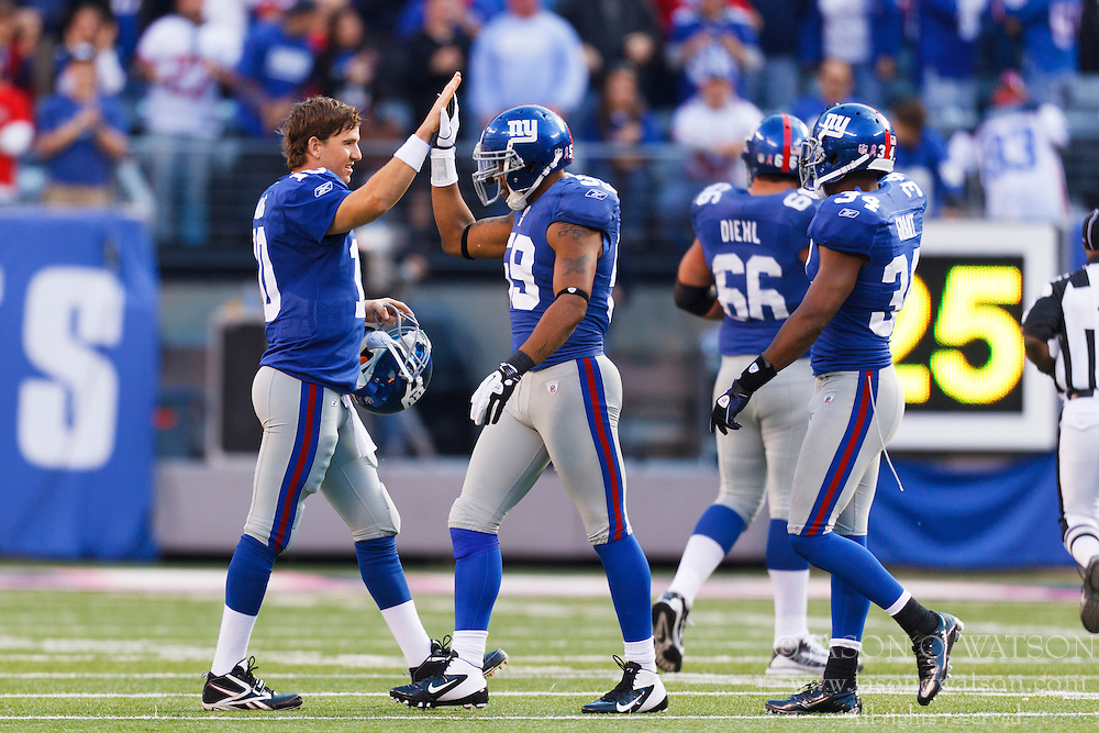 Oct 16, 2011; East Rutherford, NJ, USA; New York Giants quarterback Eli Manning (left) celebrates with outside linebacker Michael Boley (center) during the fourth quarter at MetLife Stadium. New York defeated Buffalo 27-24. Mandatory Credit: Jason O. Watson-US PRESSWIRE