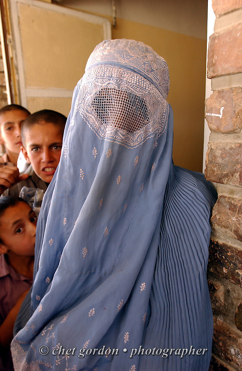 """An Afghan woman wearing the traditional burka pauses to have her portrait made in the courtyard of the Tahieya Maskan Orphanage for boys on Saturday, May 25, 2002. A humanitarian mission organized by The Geshundheit Instititute, founded by Dr. Hunter """"Patch"""" Adams, Lufthansa Cargo, and DHL Worldwide Express collaborated to ship medicines, food and orthopedic supplies to the Indira Ghandi Children's Hospital, clinics and orphanages in Kabul. The German NGO (Non Governmental Organization) Hammer Forum supervised the distribution of the donated supplies from various non-profit organizations in the U.S. and The Netherlands."""