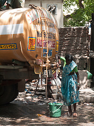 Woman drawing fresh drinking water from tanker lorry parked on Mumbai street.