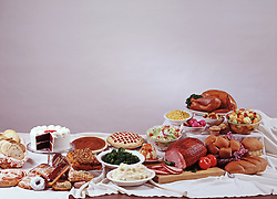 FOOD Typical PA Pennsylvania Dutch style buffet featuring pastry pastries cake pies turkey ham mashed potatos mixed vegetables salad corn red beet eggs tomatos apple dumpling bread rolls cutting board copy space