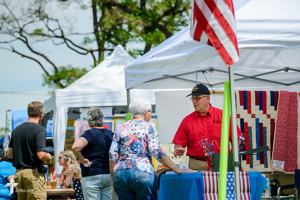 The Rev. Michael Musegades, a veteran and the pastor of Trinity Lutheran Church, Grangeville, Idaho, chats with a visitor in the TLC4Vets outreach tent at the Grangeville Border Days Independence Day celebration and parade on Tuesday, July 4, 2017, in Grangeville. LCMS Communications/Erik M. Lunsford
