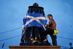 © Licensed to London News Pictures. 16/09/2014. Glasgow, UK. A man climbs on a statue to attach a Scottish Saltire flag whilst Yes voters and campaigners hold a mass meeting at George's Square in Glasgow city centre on the evening of Tuesday, 16 September, two days ahead of the Scottish independence referendum. Photo credit : Tolga Akmen/LNP